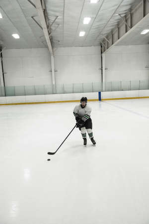 Full length of male player practicing ice hockey at illuminated rink