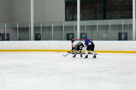 Male players playing ice hockey at rink