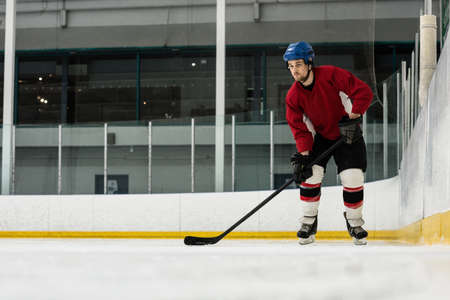 Full length of determined male player playing ice hockey at rink