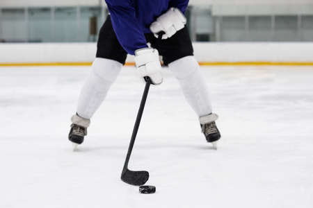 Low section of male player playing hockey at ice rink