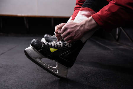 Low section of male hockey player tying ice skate in dressing room LANG_EVOIMAGES