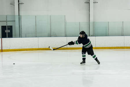 Full length of male player playing ice hockey at rink