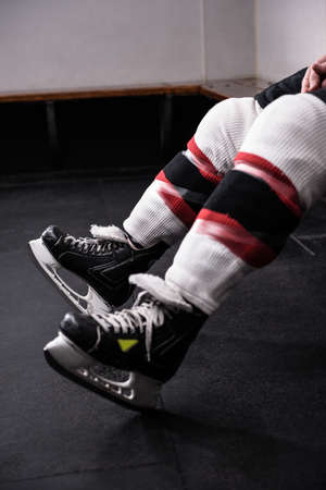 Low section of male hockey player wearing ice skates relaxing in dressing room