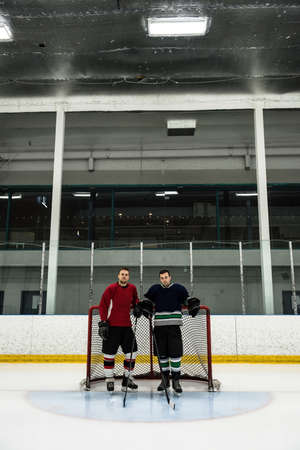 Full length of male ice hockey players standing by goal post at rink LANG_EVOIMAGES