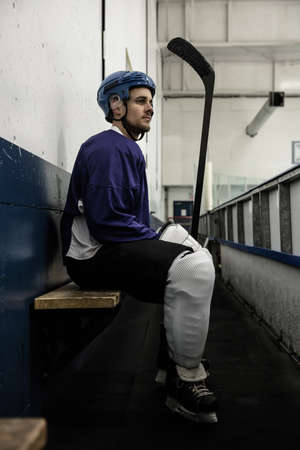 Side view full length of thoughtful ice hockey player on seat at corridor LANG_EVOIMAGES