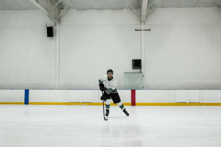 Full length of male player practicing ice hockey at rink