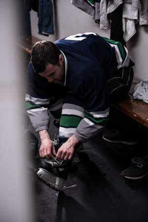 Male ice hockey player tying skate while sitting in dressing room LANG_EVOIMAGES