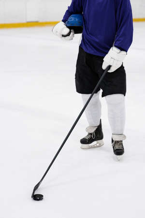 Low section of male player with ice hockey stick standing at rink