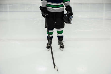 Low section of male player holding ice hockey stick and helmet at rink LANG_EVOIMAGES
