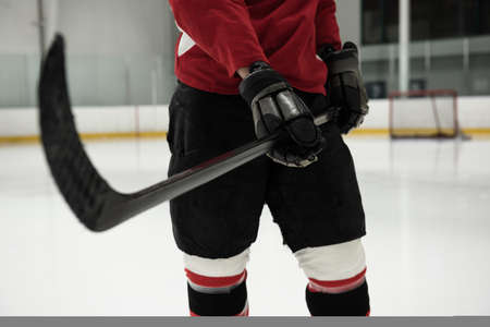 Mid section of hockey player holding stick at ice rink