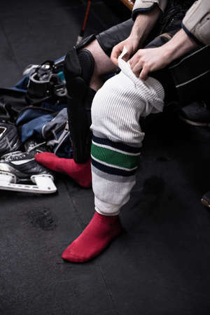 Low section of male ice hockey player wearing sock in dressing room LANG_EVOIMAGES
