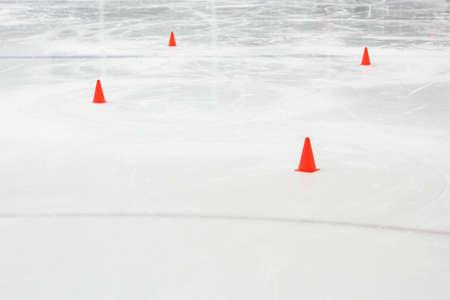 Orange sport training cones at empty ice hockey rink