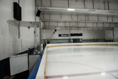 Scoreboard at empty illuminated ice hockey rink