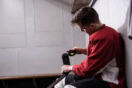 Side view of male player taping ice hockey stick while sitting in dressing room