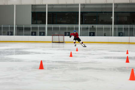 Male ice hockey player practicing drills by sport training cones at rink