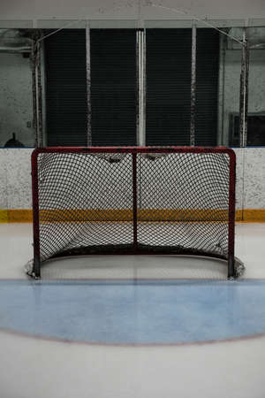 Goal post net at empty ice hockey rink LANG_EVOIMAGES