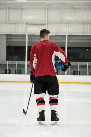 Rear view of male ice hockey player holding helmet and stick at rink