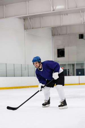 Full length of determined male player practicing ice hockey at rink