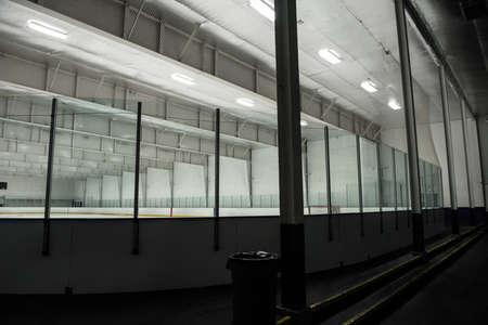 Glasses at illuminated empty ice hockey rink