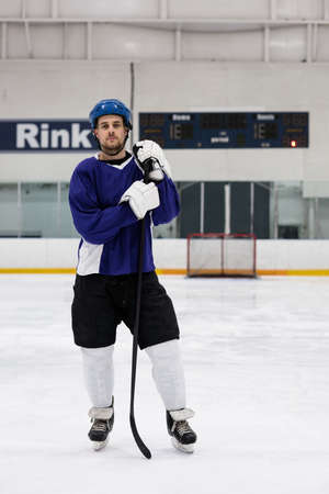 Full length portrait of male ice hockey player holding stick at rink LANG_EVOIMAGES