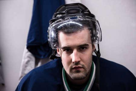 Portrait of confident male ice hockey player wearing headwear in locker room