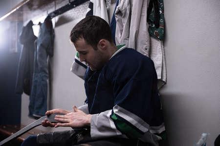 Male player holding ice hockey stick in locker room