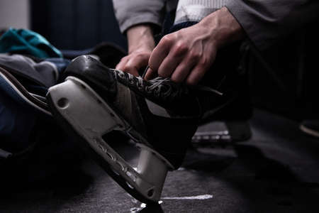 Low section of male ice hockey player tying skate in dressing room