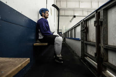 Side view full length of ice hockey player on seat at corridor