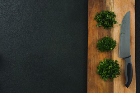 Overhead of chopped herbs with knife on chopping board