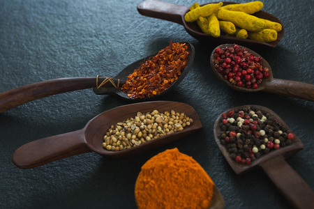 Various spices in wooden scoop on black background