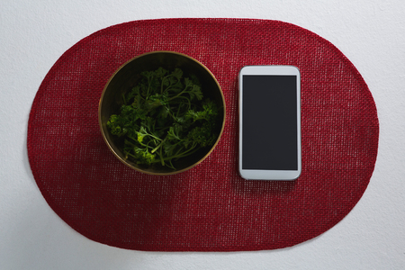 Overhead of corianders in bowl with mobile phone on place mat