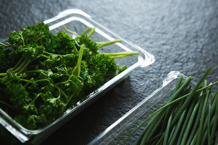 Various type of herbs in plastic tray on black background