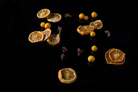 Dried sweet lemon and cape gooseberry on black background