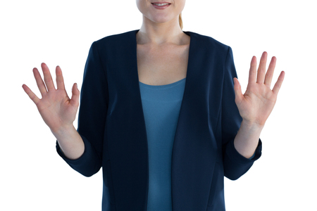 Mid section of smiling businesswoman gesturing while standing against white background Stock Photo