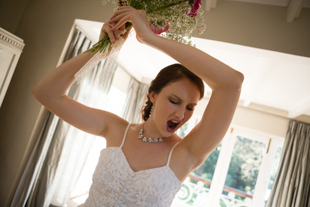 Tilt image of angry bride throwing bouquet while standing at home Stock Photo