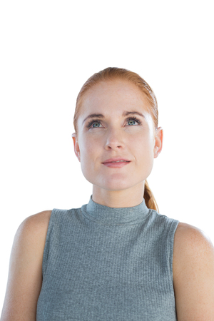 contemplated: Close up of happy thoughtful young businesswoman looking up against white background