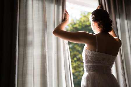 darkroom: Rear view of bride in wedding dress looking through window while standing at home Stock Photo