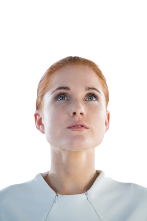 contemplated: Close up of thoughtful businesswoman looking up while standing against white background