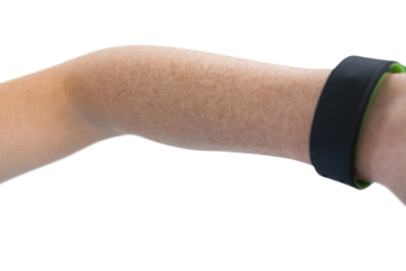 Cropped hand on woman with fitness band against white background