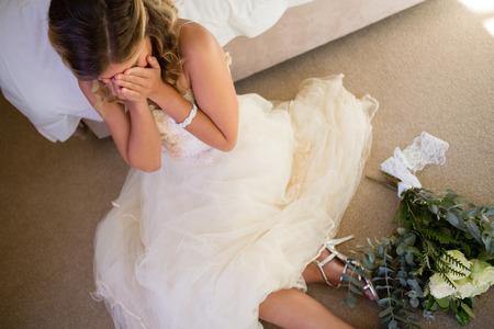 Hoge hoek weergave van bruid in trouwjurk huilen tijdens het zitten bij bed thuis