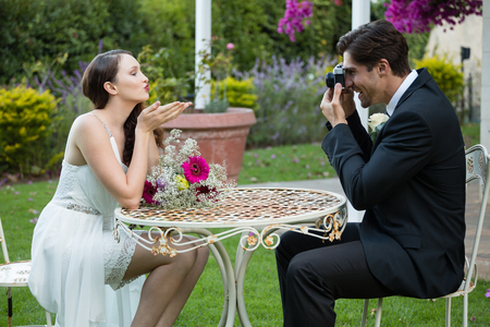 Side view of bridegroom photographing bride blowing kiss while sitting at table in park