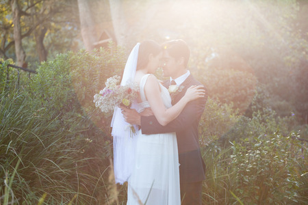Romantic newlywed couple with eyes closed embracing while standing in park