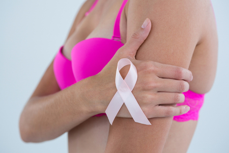 Side view of woman Breast Cancer Awareness ribbon standing against gray background