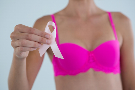 Mid section of woman showing Breast Cancer Awareness ribbon while standing against gray background