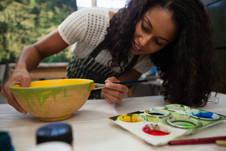 Beautiful woman painting bowl in drawing class