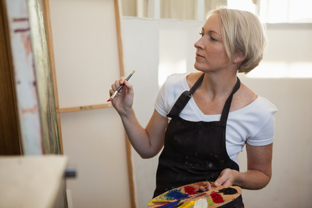 Woman painting on canvas in drawing class Stock Photo