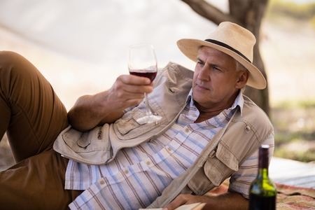 Man having wine in cottage during safari vacation Stock Photo