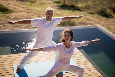 Portrait of happy couple practicing yoga on at poolside on a sunny day