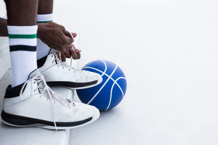Low section basketball player tying shoelace