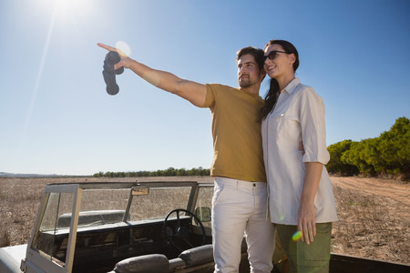 Young man with woman pointing while standing on vehicle at landscape during sunny day Stock Photo